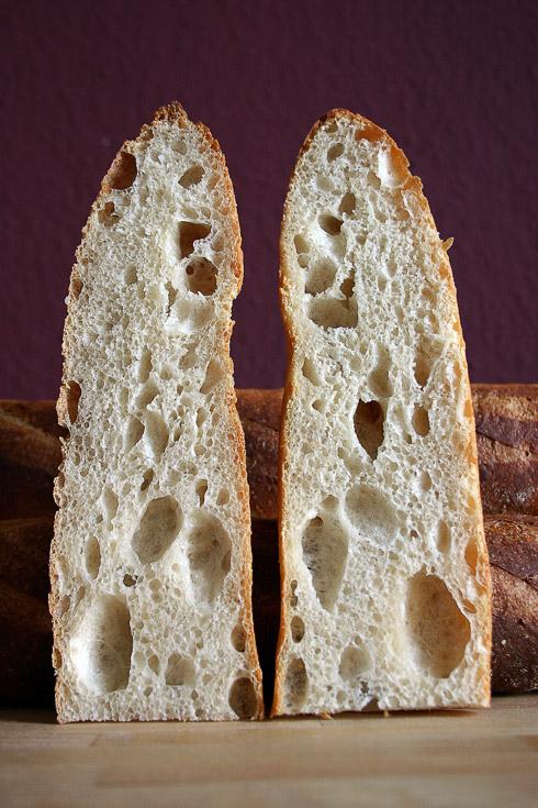 Offene, ungleichmäßige, aromatische Krume dank der Kombination von Weizensauerteig (Levain) und Poolish. Die Kruste des Baguettes ist dünn und knusprig.