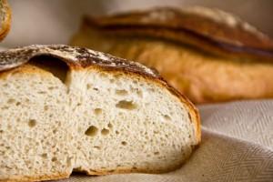 Fein- bis mittelporige Krume. Im Hintergrund das Brot in Tabatière-Form.