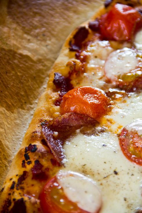 Belegt mit Tomaten und Mozarella: Pizzateig