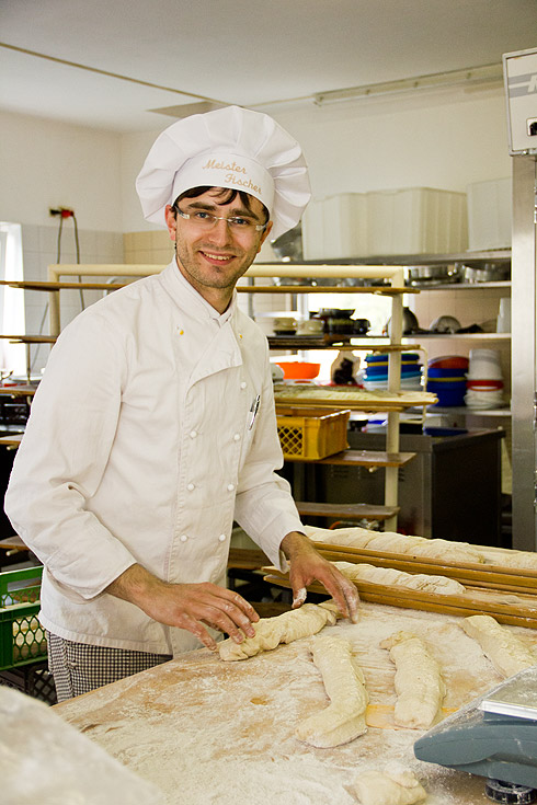 Während der Ofen nochmals aufgeheizt wird, dreht Ricardo Fischer seine Zwirbelbaguettes beim Schaubacken.