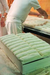 Der Bäckermeister nimmt die reif geteilten Teiglinge aus der Kiste und legt sie auf den Abziehapparat des Ofens.