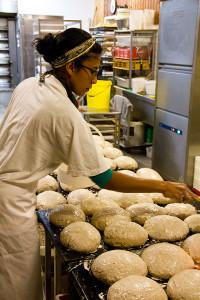 Zayaan in der Backstube beim Abstreichen der Gersterbrote mit Mehlstreiche