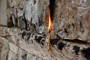 Bevor die Flamme den Finger als Docht nutzt, wird sie an die Kirchenmauer gepresst...