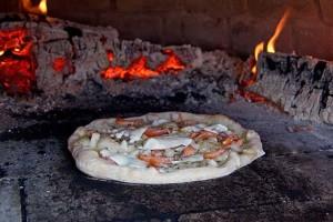 Lachs-Pizza mit Olivenöl und Mozarella im Ofen.