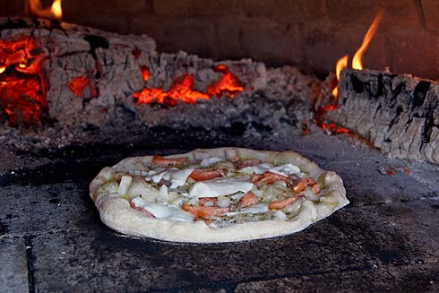 Lachs-Pizza mit Olivenöl und Mozzarella im Ofen.